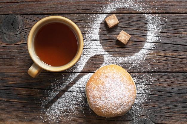 Tasse schwarzen tee und donut mit puderzucker auf der tischoberansicht