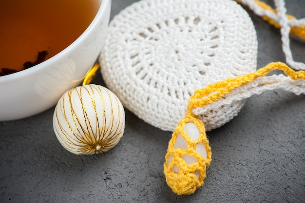 Tasse schwarzen tee und gehäkelte kieselsteine
