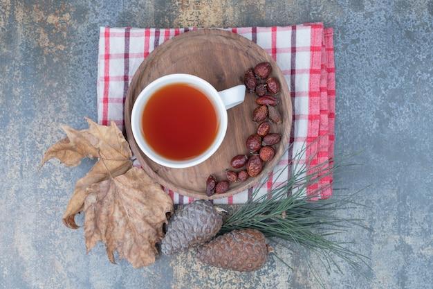 Tasse schwarzen tee und getrocknete hagebutten auf holzteller mit tannenzapfen. hochwertiges foto
