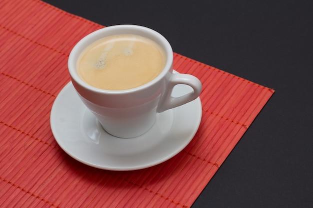 Tasse schwarzer kaffee auf untertasse und bambusserviette mit schwarzem hintergrund. ansicht von oben.