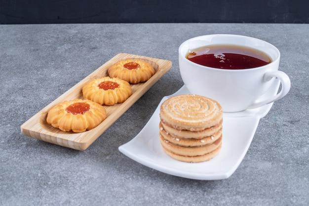 Tasse schwarzer tee mit leckeren keksen auf marmoroberfläche