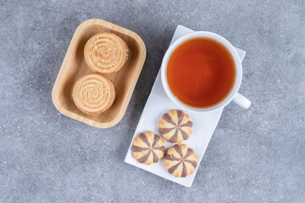 Tasse schwarzer tee mit verschiedenen keksen auf marmoroberflächek