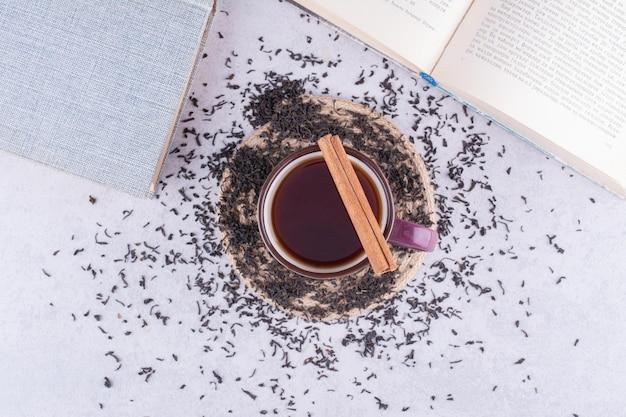 Tasse schwarzer tee mit zimtstange und trockenem tee. foto in hoher qualität
