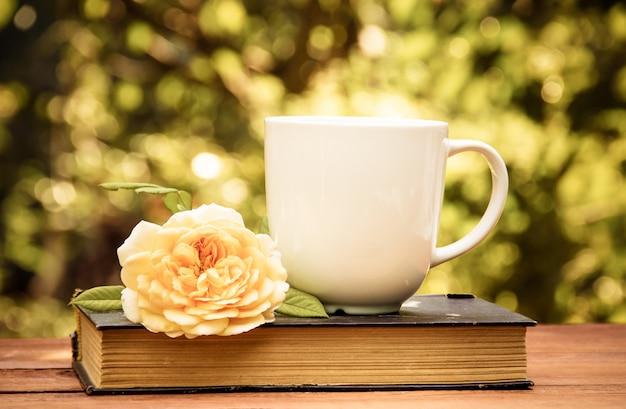 Tasse tee, altes buch und rose im sommergarten