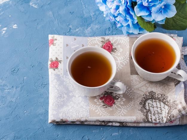 Tasse tee auf blauem hintergrund mit blumen und gewebe