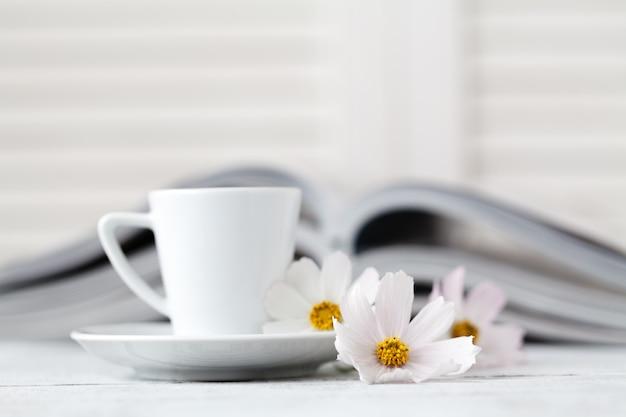 Tasse tee auf buch mit blume.