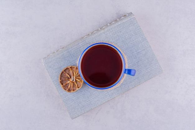 Tasse tee auf buch mit orangenscheibe. foto in hoher qualität