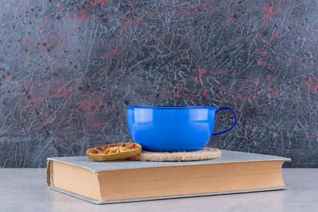 Tasse tee auf buch mit orangenscheibe.