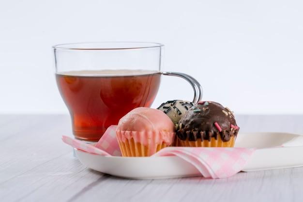 Tasse tee auf einem holztisch in hellem und weißem ton, begleitet von einem teller mit mini-cupcakes, die mit dunkler erdbeerschokolade und weißer schokolade überzogen sind