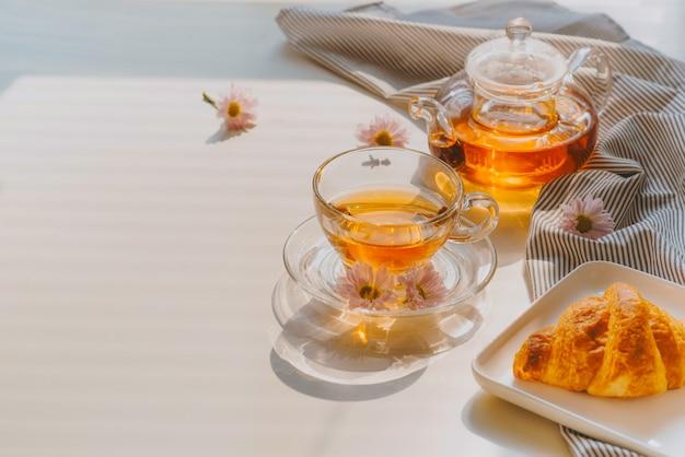 Tasse tee auf einem tablett und zweigen mit blumen auf einem tisch in der nähe eines fensters eines sonnigen sommermorgens
