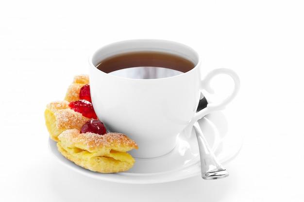 Tasse tee auf einer untertasse und kuchen