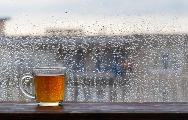 Tasse tee auf fenster mit regentropfen bei sonnenuntergang