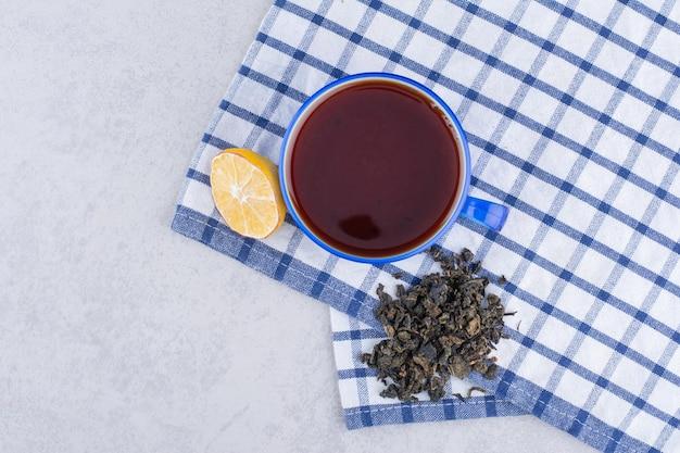 Tasse tee auf tischdecke mit zitronenscheibe. foto in hoher qualität