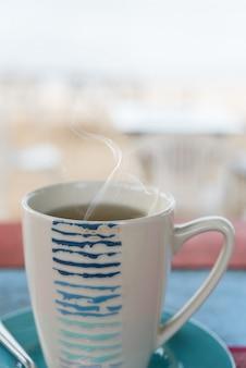 Tasse tee auf vintage holztisch mit unscharfem meeresstrand