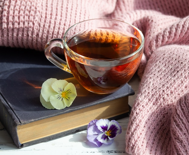 Tasse tee, buch und blumen auf hellem holztisch. lesekonzept.
