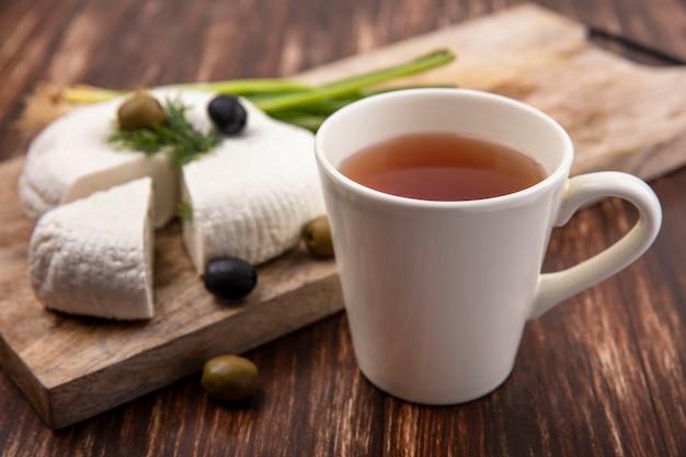 Tasse tee der seitenansicht mit feta-käse mit oliven und frühlingszwiebeln auf einem stand auf einem hölzernen hintergrund
