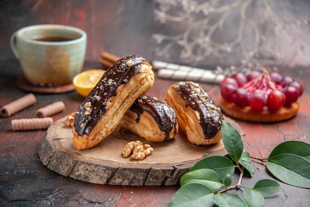 Tasse tee der vorderansicht mit köstlichen schoko-eclairs auf dunklem hintergrund
