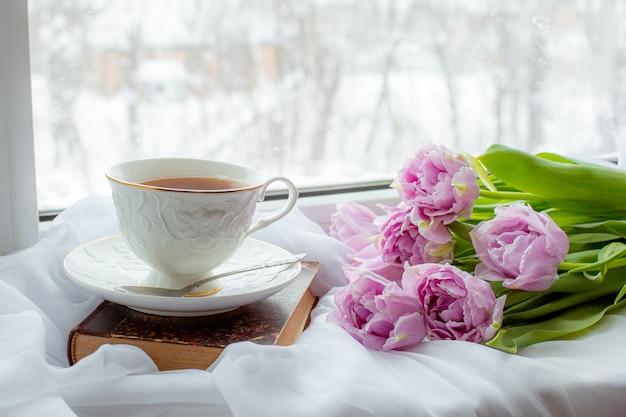 Tasse tee ein altes buch ein strauß tulpen am fenster