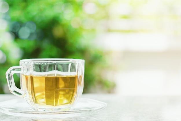 Tasse tee gegen unscharfen natürlichen grünen hintergrund für getränke und getränkkonzept