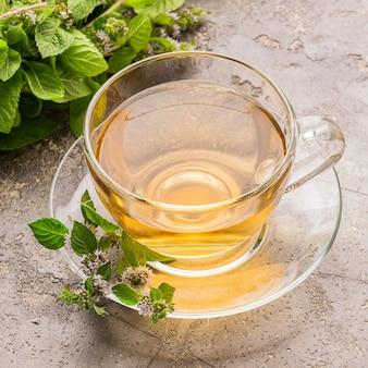 Tasse tee getränk mit frischen blättern der pfefferminzmelisse grau