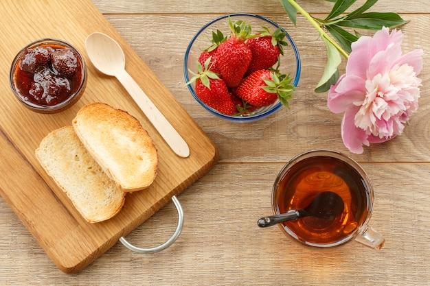 Tasse tee, hausgemachte erdbeermarmelade und frische beeren in glasschalen, holzlöffel, toast auf schneidebrett und pfingstrose. ansicht von oben.