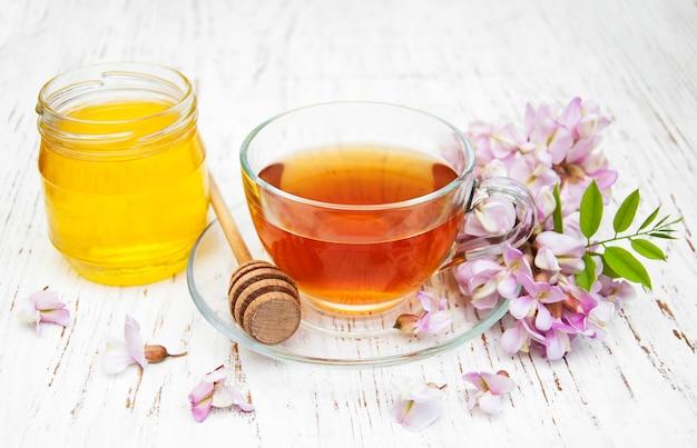 Tasse tee, honig und akazienblumen