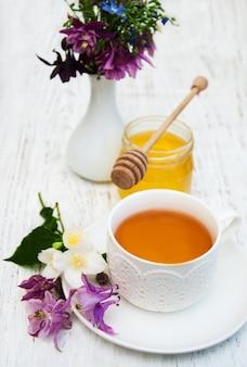 Tasse tee, honig und blumen
