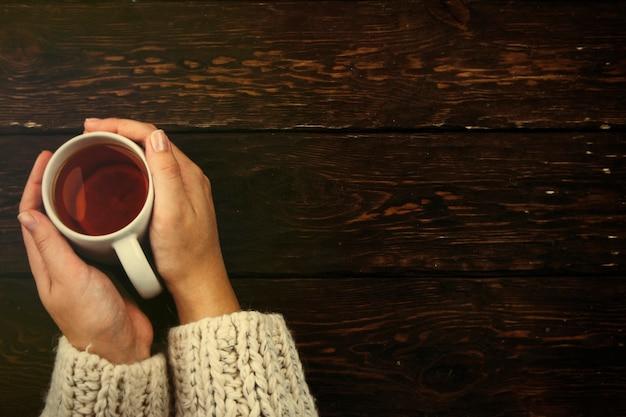 Tasse tee in den händen auf einem hölzernen hintergrund das konzept eines gemütlichen herbstes