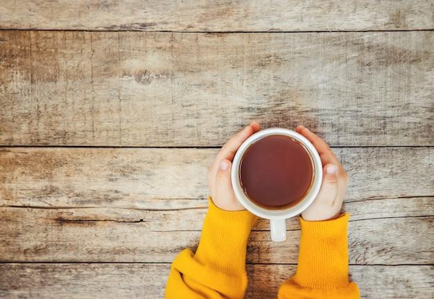 Tasse tee in den händen eines kindes und ein gemütlicher herbsthintergrund. selektiver fokus