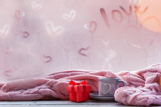 Tasse tee, kaffee oder heiße schokolade und rosa plaid auf nebeligem fenster mit liebestext. valentinstag und liebe konzept.