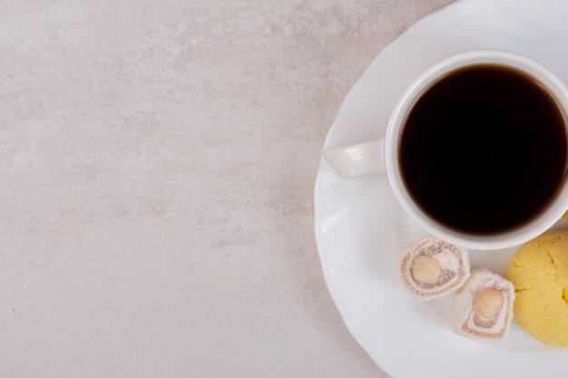 Tasse tee, köstlichkeiten und kekse auf weißem tisch.