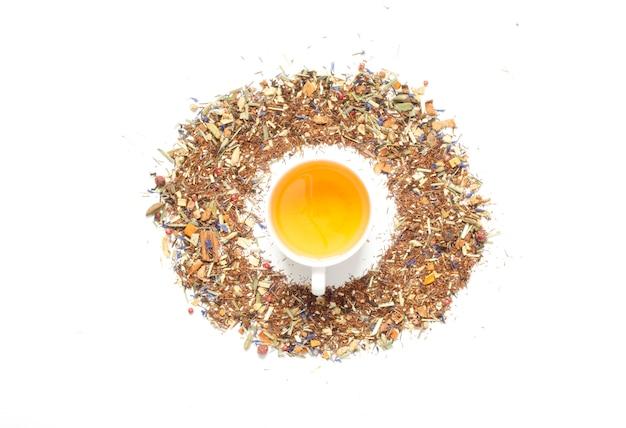 Tasse tee. kräutertee, trockene kräuter und blüten mit fruchtstücken und beeren. ansicht von oben.