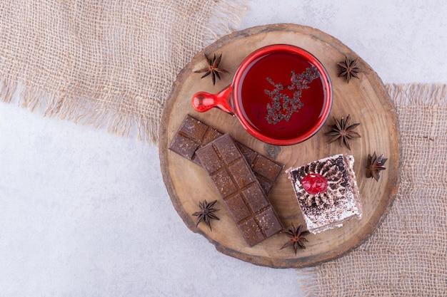 Tasse tee, kuchenscheibe und schokoriegel auf holzstück. foto in hoher qualität