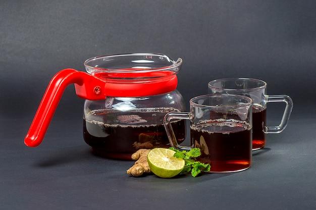 Tasse tee, minze und zitrone auf dunklem tisch