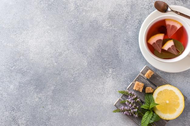 Tasse tee, minze und zitrone auf grauer tabelle mit kopienraum