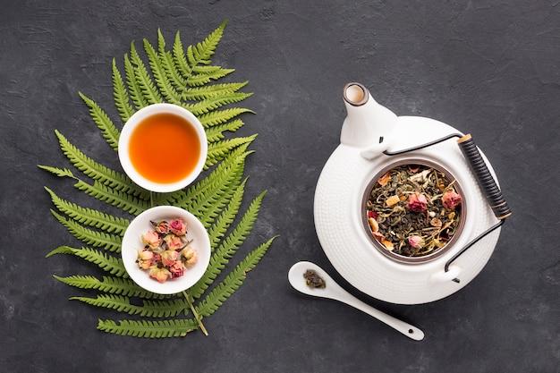 Tasse tee mit aromatischem trockenem tee in den schüsseln auf schwarzem steinhintergrund