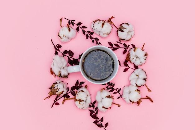 Tasse tee mit baumwolle auf rosa hintergrund. ansicht von oben