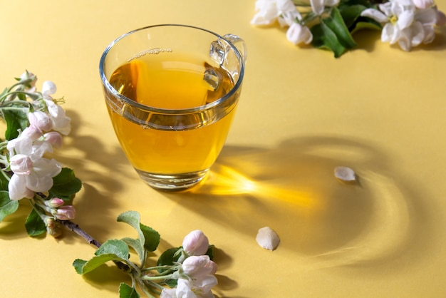 Tasse tee mit blumen des apfelbaums auf einem hellgelben hintergrund