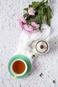 Tasse tee mit blumenhintergrund mit den roten und weißen tulpen und den gänseblümchen