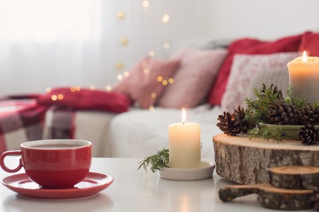 Tasse tee mit brennenden kerzen auf weißem tisch