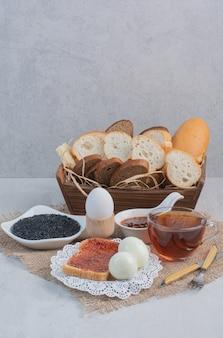 Tasse tee mit brot und eiern auf sackleinen.