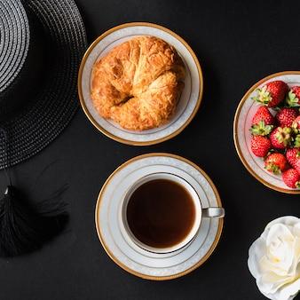 Tasse tee mit brot und erdbeere auf schwarzem hintergrund