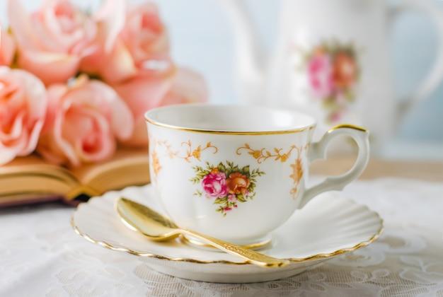 Tasse tee mit buch, teekanne und rosafarbenen blumen auf blau