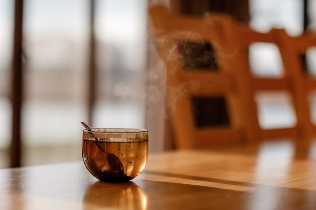 Tasse tee mit dampf auf holztisch im wohnzimmer. selektiver fokus