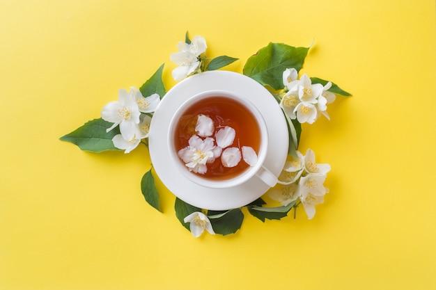 Tasse tee mit den blumenblättern des jasmins blüht auf einem hellen gelb