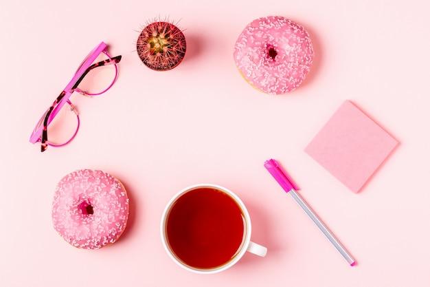 Tasse tee mit doand-nüssen auf einem rosa pastellhintergrund