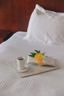 Tasse tee mit einem buch auf einem weißen tablett mit einer gelben blume auf einem weißen bett