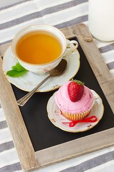 Tasse tee mit einem cupcake mit frischer erdbeere in teller