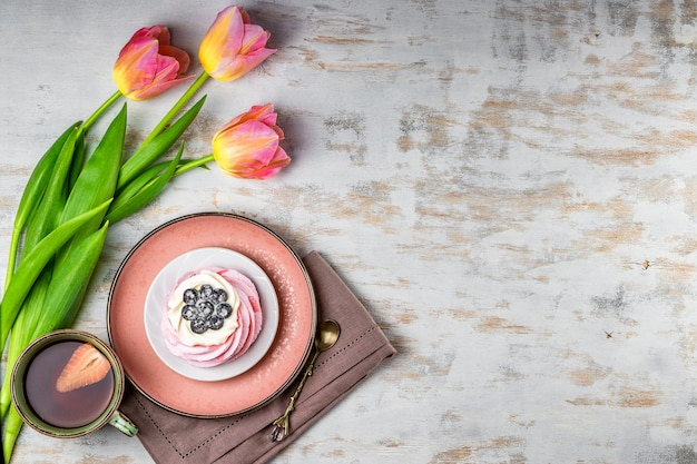 Tasse tee mit erdbeeren, pavlova-kuchen und rosa tulpen auf weißem holz