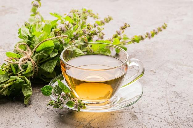 Tasse tee mit frischen blättern